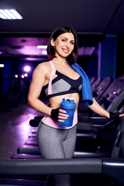 Portrait of a healthy middle age fitness woman holding water bottle shaker in gym Premium Photo