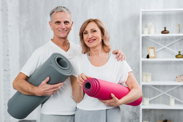 Portrait of a healthy senior couple with yoga mat standing at home Free Photo