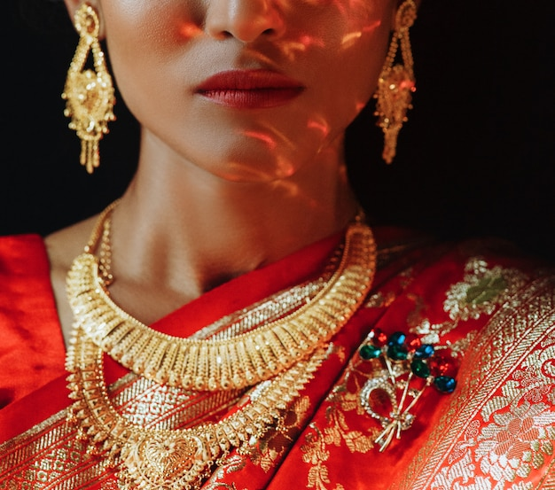 Portrait of hindu bride in traditional red sari with golden acce Free Photo