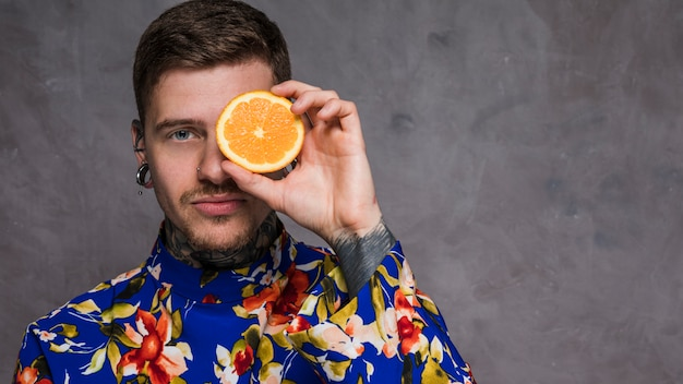 Portrait of a hipster young man holding juicy orange in front of his eyes Free Photo