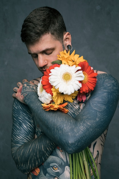 Portrait of a hipster young man with tattooed on his body embracing the gerbera flowers Free Photo