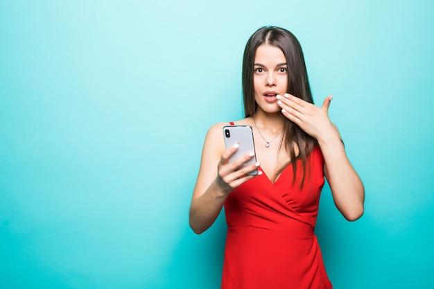 Ritratto se una giovane ragazza scioccata in abito guardando il telefono cellulare isolato sopra la parete blu Foto Gratuite