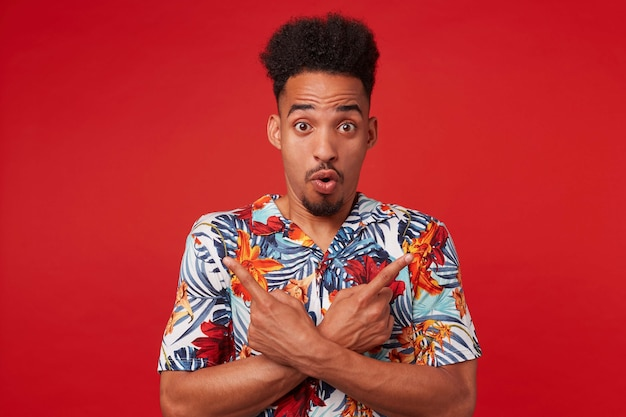 Portrait if young shocked african american man in hawaiian shirt, looks at the camera with surprised expression, stands over red background, points in different directions. Free Photo