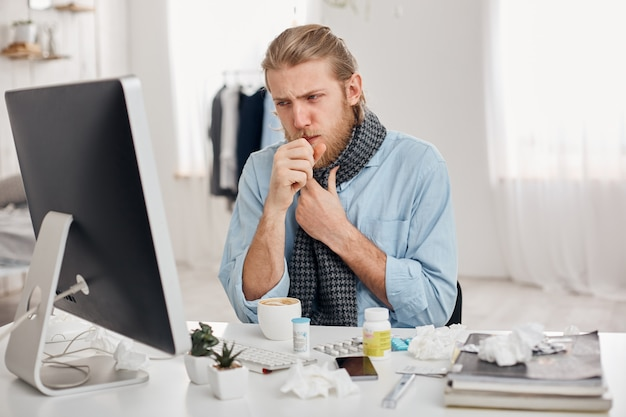 Portrait of ill sick bearded male manager coughs, has cold and flu. young fair-haired man has running nose, cough and bad cold, sits at workplace in front of computer screen. illness and infection Free Photo