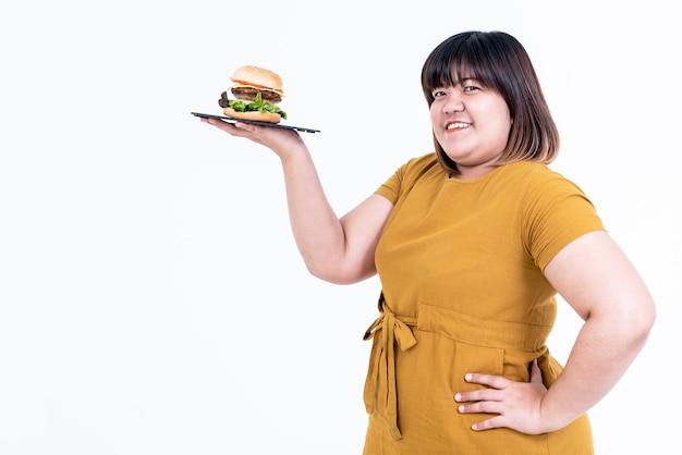 아시아 매력적인 뚱뚱한 여자의 초상화 이미지는 행복하고 미소 짓고 햄버거를 들고 있습니다. 프리미엄 사진