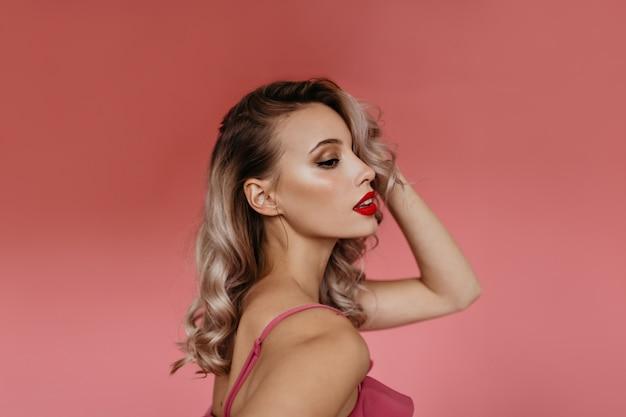 Портрет в профиль в студии красивой молодой блондинки с вьющимися волосами и ярко раскрашенными розовыми губами, позирующей перед камерой, показывая свои нежные женственные плечи Бесплатные Фотографии