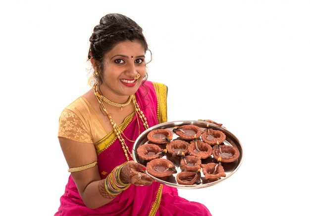 Portrait of a indian traditional girl holding diya, diwali or deepavali photo with female hands holding oil lamp during festival of light on white surface Premium Photo