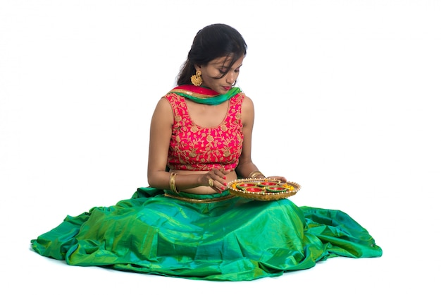 Portrait of a indian traditional girl holding diya, girl celebrating diwali or deepavali with holding oil lamp during festival of light on white surface Premium Photo