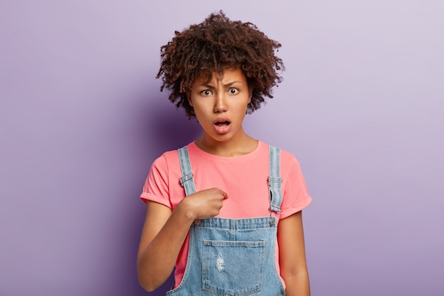 Portrait of indignant dissatisfied dark skinned woman points at herself, has puzzled expression, asks why me, being accused of something, wears t shirt and overalls models indoor has negative reaction Free Photo