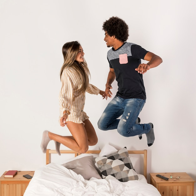 Portrait of interracial couple jumping in bed Free Photo