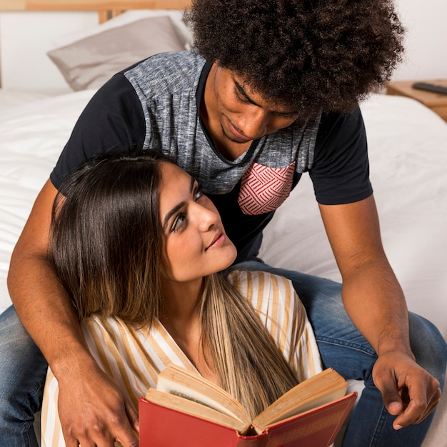 Portrait of interracial couple reading together Free Photo