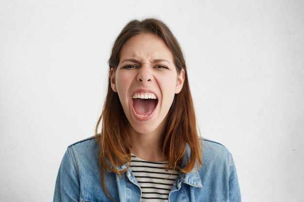 Ritratto di donna arrabbiata irritata con capelli scuri dritti che aggrotta le sopracciglia il viso aprendo ampiamente la bocca esprimendo la sua insoddisfazione. Foto Gratuite