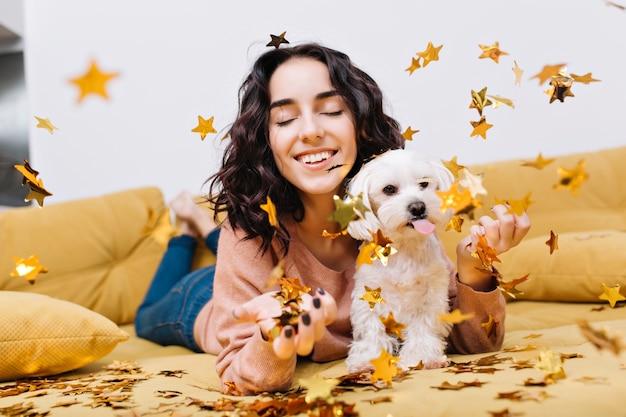 立ち下がり黄金の見掛け倒しで目を閉じて笑って肖像画うれしそうな素晴らしい若い女性。家庭用ペット、小さな白い犬、笑顔、陽気な気分、リラクゼーションでソファでくつろぐ 無料写真