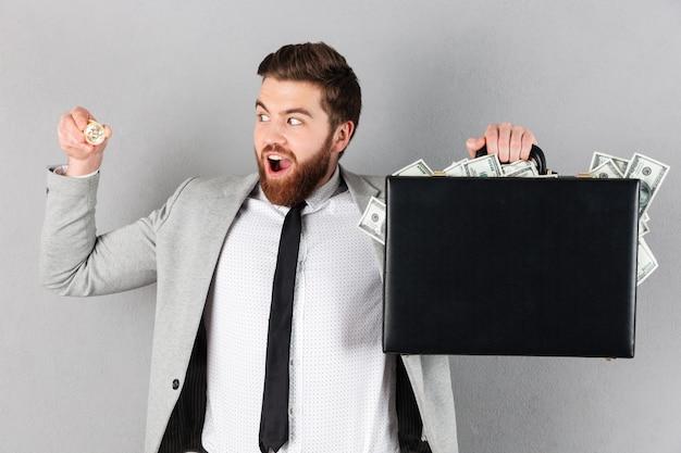Portrait of a joyful businessman showing golden bitcoin Free Photo