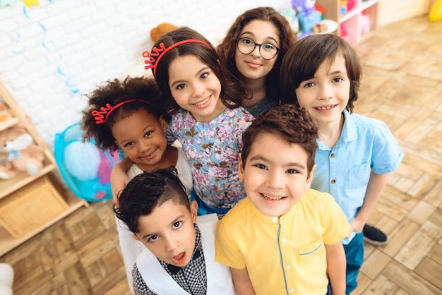 Portrait of joyful children in holiday hats at birthday party Premium Photo
