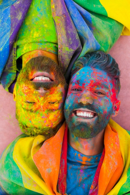 Portrait of joyful gay couple in love soiled in paint Free Photo