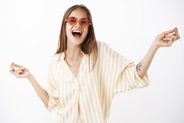 Portrait of joyful happy and amused carefree stylish woman in trendy red sunglasses and yellow striped blouse dancing singing song out loud with broad smile and hands spread aside Free Photo