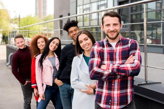Ritratto di gioiosi amici multirazziali in piedi in fila vicino a ringhiera in strada Foto Gratuite