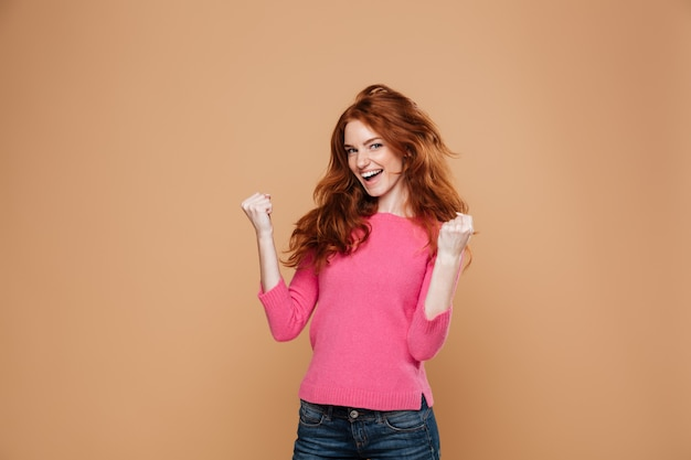 Portrait of a joyful satisfied redhead girl celebrating victory Free Photo