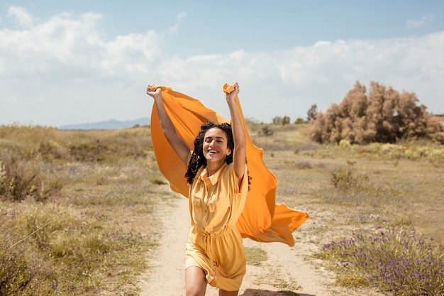Portrait of joyful woman with yellow cloth in nature Free Photo