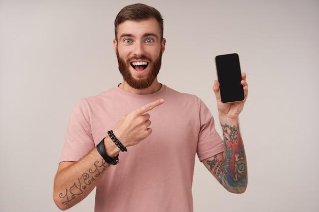 Ritratto di gioioso giovane barbuto uomo bruna con tatuaggi con occhi spalancati e bocca aperta e mostrando con l'indice sul suo smartphone in mano alzata, isolato su bianco Foto Gratuite