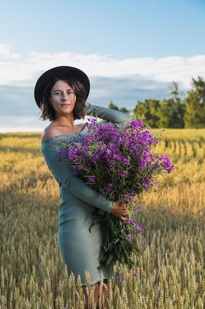 ウォーキングとフィールドの美しい自然で休んで紫の花の花束と青いドレスの肖像画うれしそうな若い女性ブルネット。スタイリッシュな流行に敏感な女性。屋外の雰囲気のあるライフスタイルの写真 Premium写真