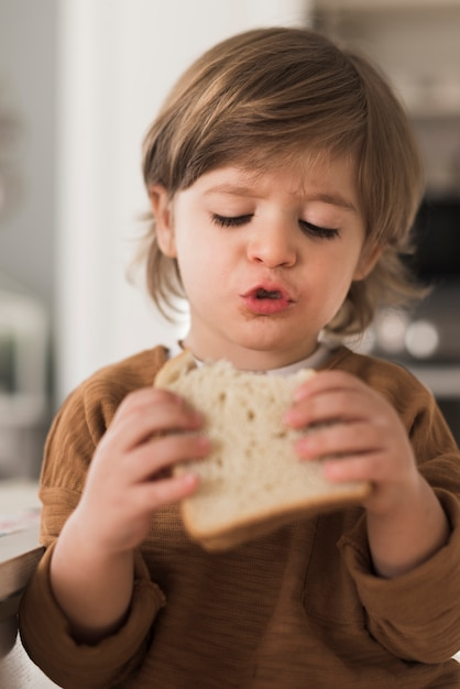 Portrait of kid eating sandwich Free Photo