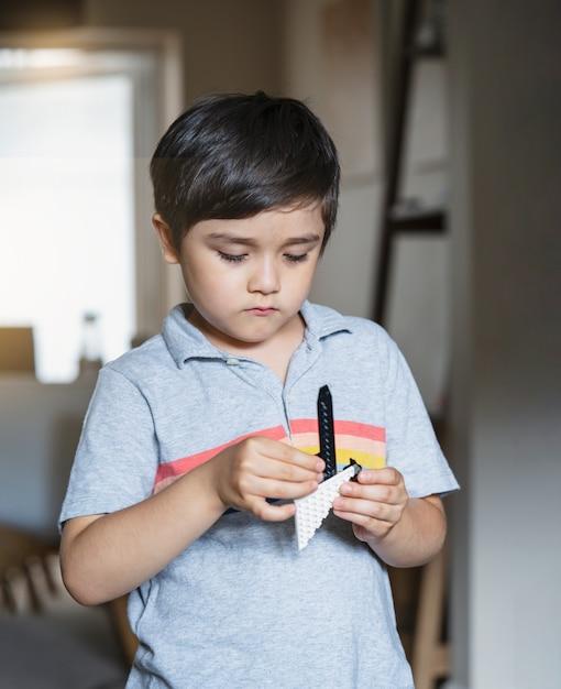 プラスチック製のブロックを遊んでいる肖像画の子供、リビングルームに立っている子少年は彼のおもちゃを作り出す集中 Premium写真