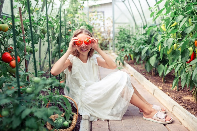 Portrait of kid with the big tomato in hands in greenhouse Premium Photo