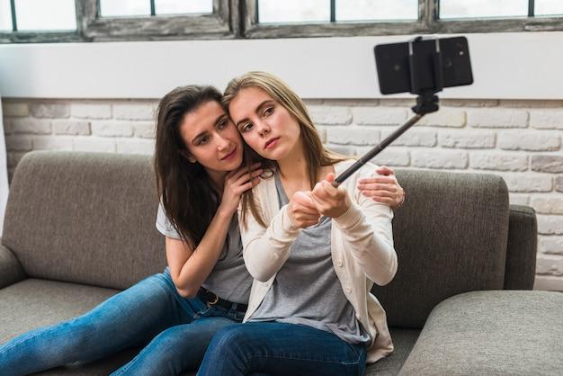 Portrait of a lesbian young couple sitting on sofa taking selfie on mobile phone Free Photo