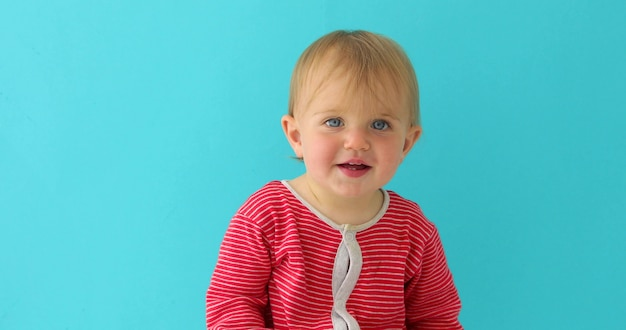 Portrait of a little 11 month old girl smiling and looking at camera on a blue background Premium Photo