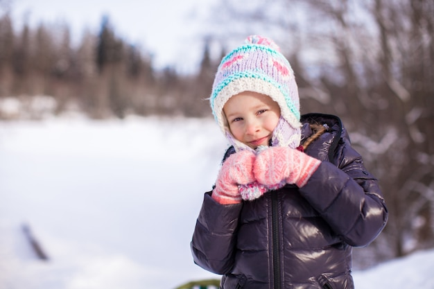 Portrait of little adorable happy girl in the snow sunny winter day Premium Photo