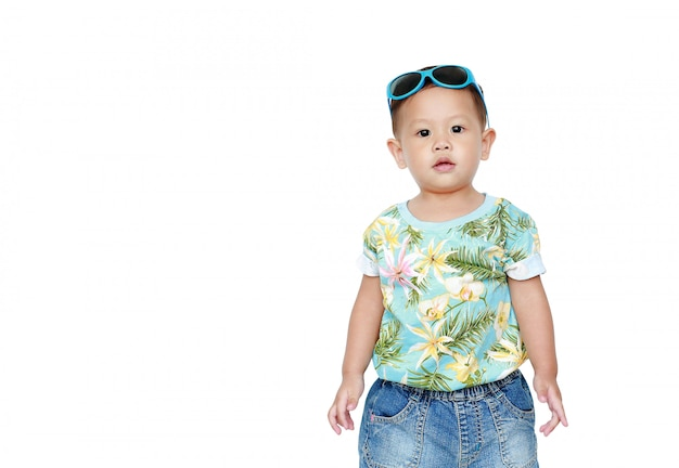 Portrait little asian baby boy wearing a flowers summer dress and sunglasses isolated. summer and fashion concept. Premium Photo