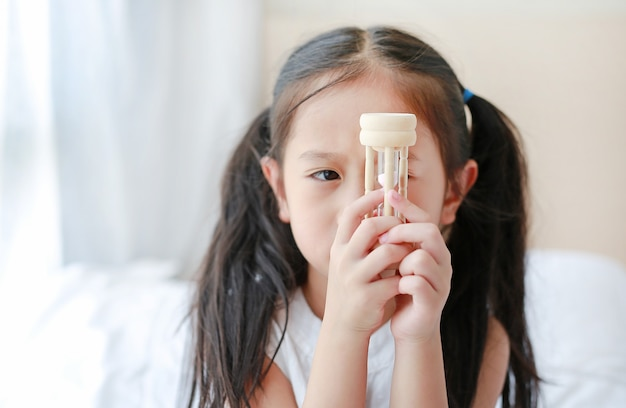 Portrait of little asian girl looking at hourglass in hand lying on bed at home Premium Photo