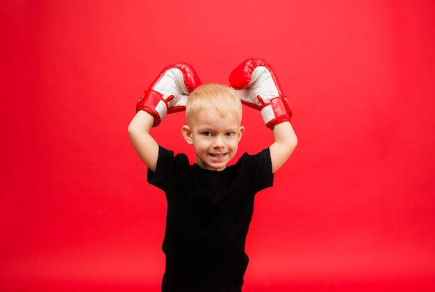 Portrait of a little boy boxing champion in red boxing gloves raised his hands up on a red wall Premium Photo