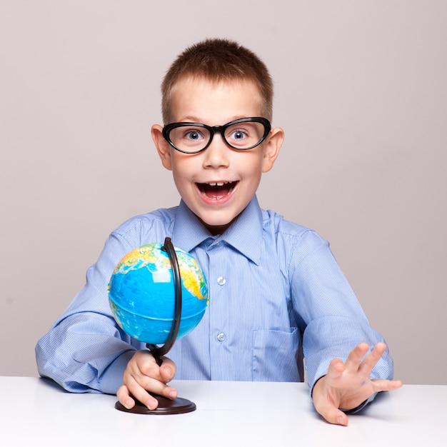 Portrait of a little boy holding a globe. travel concept Premium Photo