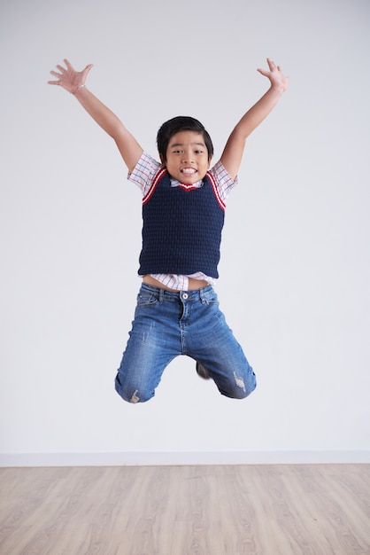 Portrait of little boy jumping happily high in the air Free Photo
