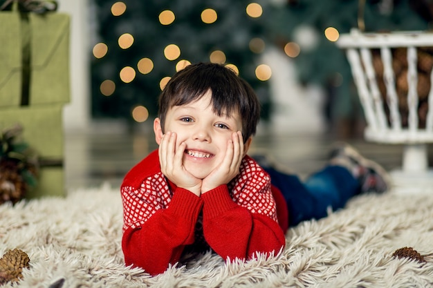 Portrait of a little boy play with pine cones near a christmas tree. christmas decorations. merry ch