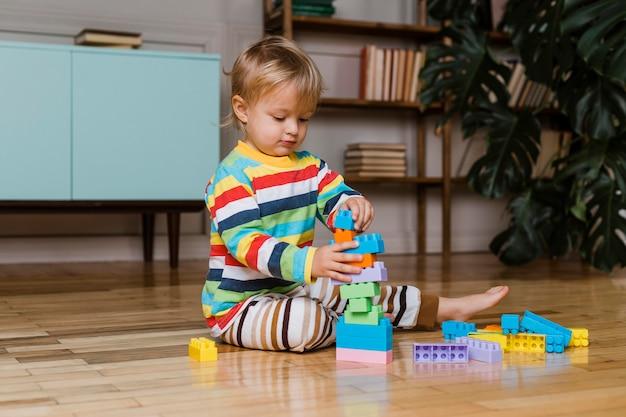 おもちゃで遊ぶ肖像画の小さな男の子 無料写真