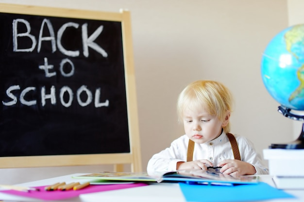 Portrait of little boy reading book at workplace. Premium Photo
