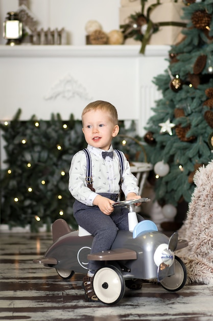 Portrait of a little boy sitting on a vintage toy airplane near a christmas tree. christmas decorations. the boy rejoices at his christmas present. merry christmas and happy new year Premium Photo