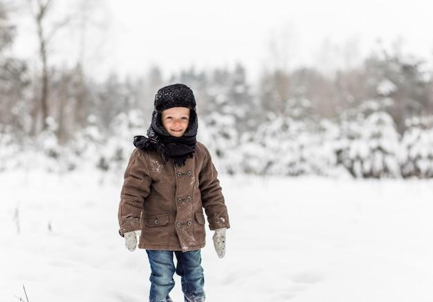 Portrait of a little boy in a winter forest Premium Photo