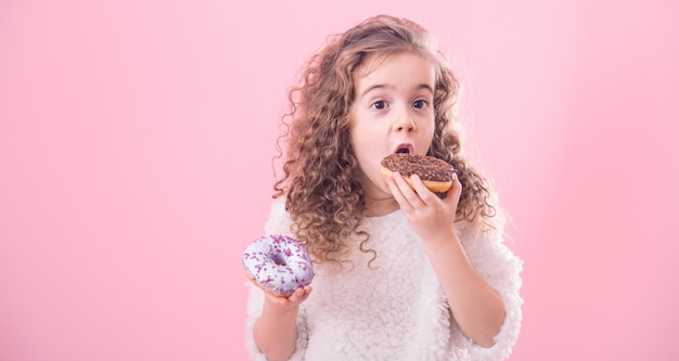 Portrait of a little curly girl eating donuts Free Photo