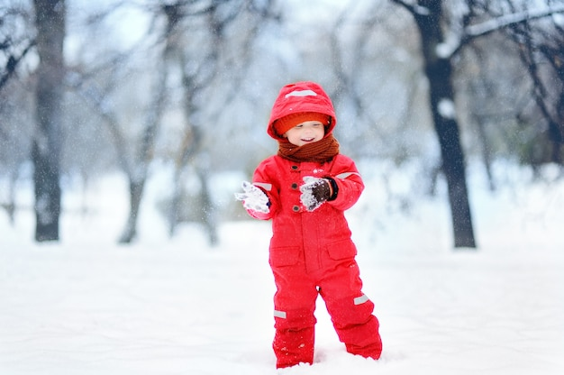 Portrait of little funny boy in red winter clothes having fun with snow during snowfall. Premium Photo