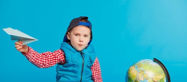 Portrait of little funny school boy with toy paper plane Premium Photo