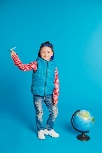 Portrait of little funny school boy with toy paper plane Premium Photo