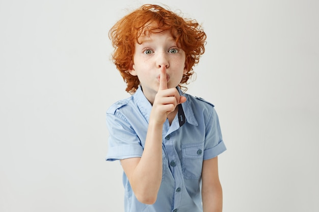 Portrait of little ginger boy with curly hair and freckles holding finger near lips Free Photo