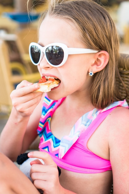 Portrait of little girl eating pizza in outdoor cafe at dinner Premium Photo