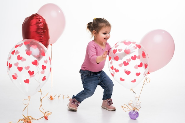 Portrait of little girl playing with balloons Free Photo
