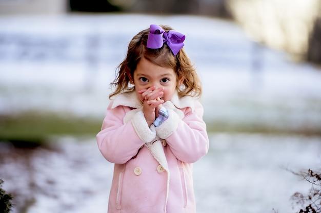 Ritratto di una bambina che prega in un parco coperto di neve sotto la luce del sole Foto Gratuite